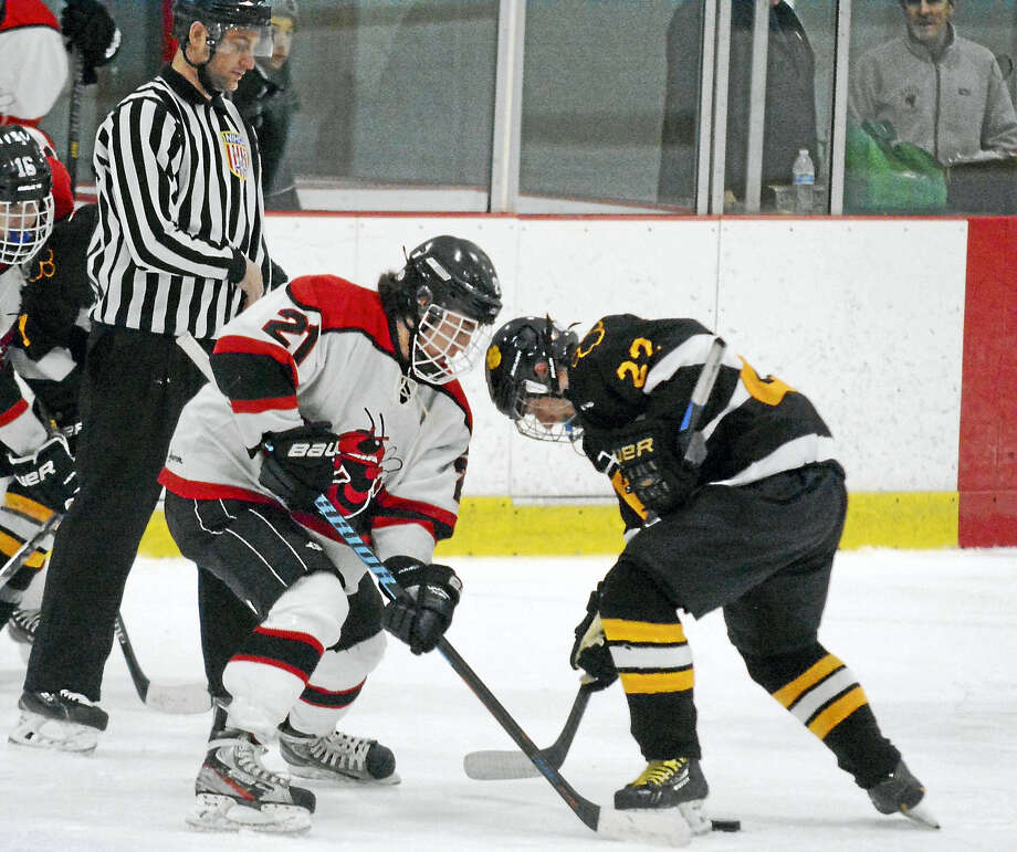 Branford's Scott Klouda, left, and Hand's Tristan Sorensen battle in a face-off during Hand's 8-2 win Saturday night. Photo: Dave Phillips — GameTimeCT