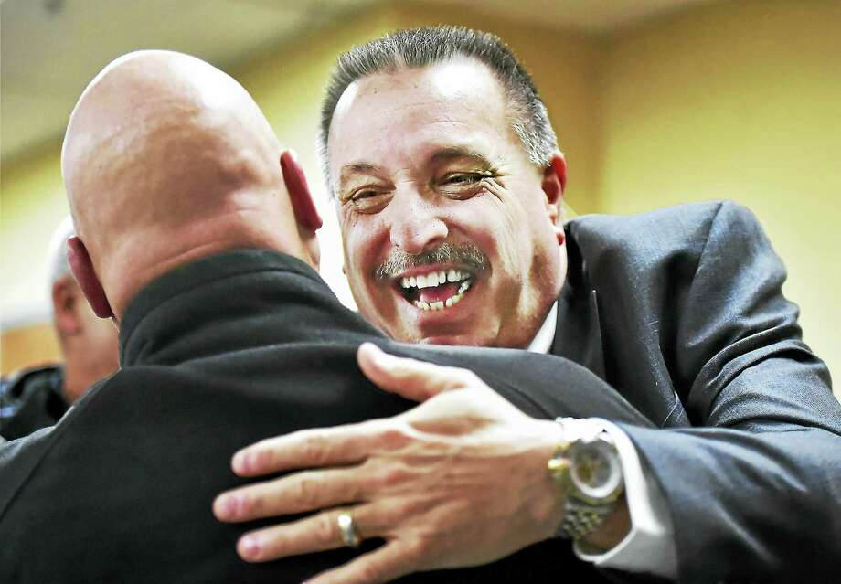 Detective Sgt. Bill Cole, left, wishes retiring Detective Sgt. Paul Raucci well Tuesday in the community room at the West Haven Police Department. Photo: Catherine Avalone — New Haven Register      / New Haven RegisterThe Middletown Press