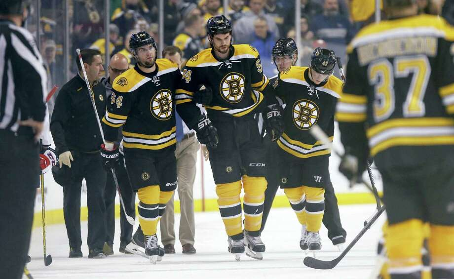 Boston Bruins' Adam McQuaid (54) leaves the ice after being injured during the second period of an NHL hockey game against the Washington Capitals in Boston, Tuesday, Jan. 5, 2016. (AP Photo/Michael Dwyer) Photo: AP / AP
