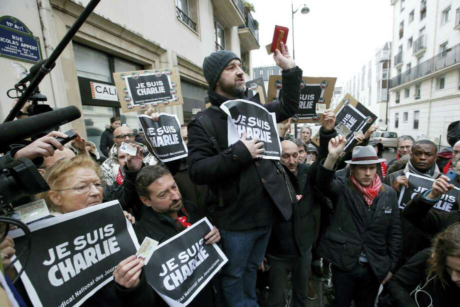 "In this Thursday, Jan. 8, 2015, file photo, journalists hold up their press cards during a minute of silence outside the Charlie Hebdo newspaper in Paris, a day after masked gunmen stormed the office. Seventeen people died at Charlie Hebdo on Jan. 7, 2015, and at a kosher supermarket two days later. They were among the first victims of a string of attacks by Islamic fundamentalists in France last year that ultimately left at least 147 people dead and hundreds of others injured. In a special edition marking the anniversary of the Jan. 7 attack on the paper's staff,  Charlie Hebdo's surviving artists and writers declared that the satirical newspaper is alive, but ""the murderer is still at large."" Photo: AP Photo/Francois Mori, File    / AP"