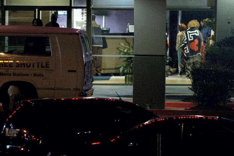 People stand in a motel lobby at the Rite4Us Inn and Suites on Snapfinger Woods Drive, Tuesday, Jan. 5, 2016, in DeKalb County, Ga. A standoff at the motel outside Atlanta that involved a number of children ended Tuesday morning with the suspect stabbing himself but no one else injured, police said. A standoff at a motel outside Atlanta that involved a number of children ended Tuesday morning with the suspect stabbing himself but no one else injured, police said. DeKalb County interim Police Chief James Conroy tells WSB-TV the man was armed with a knife. Police later identified him as Korrie Thomas, 36, and said he is facing charges of false imprisonment and obstruction. Photo: Branden Camp/Atlanta Journal-Constitution Via AP    / GAATJ