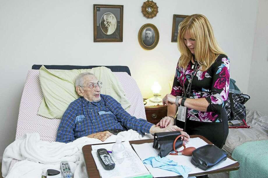 PHOTO BY DEREK TORRELLAS  Nurse Jeanette Hutchinson checks U.S. Army veteran Bob Swirsky's vital signs, during a home care visit. Photo: Journal Register Co.