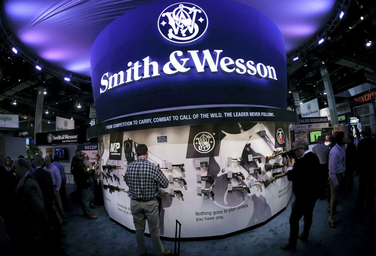 In this Jan. 14, 2014 photo, trade show attendees examine handguns and rifles in the Smith & Wesson display boot at the Shooting Hunting and Outdoor Tradeshow, in Las Vegas. With all major markets in a severe sell-off Monday, Jan. 4, 2016, shares of companies that make guns surged as new data pointed to strong sales at the close of 2015, a year marked by mass shootings in Paris and California, and new political pressure to tighten regulations.