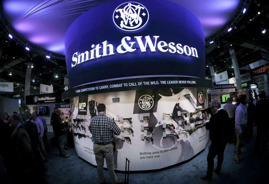 In this Jan. 14, 2014 photo, trade show attendees examine handguns and rifles in the Smith & Wesson display boot at the Shooting Hunting and Outdoor Tradeshow, in Las Vegas. With all major markets in a severe sell-off Monday, Jan. 4, 2016, shares of companies that make guns surged as new data pointed to strong sales at the close of 2015, a year marked by mass shootings in Paris and California, and new political pressure to tighten regulations. Photo: AP Photo/Julie Jacobson, File   / AP