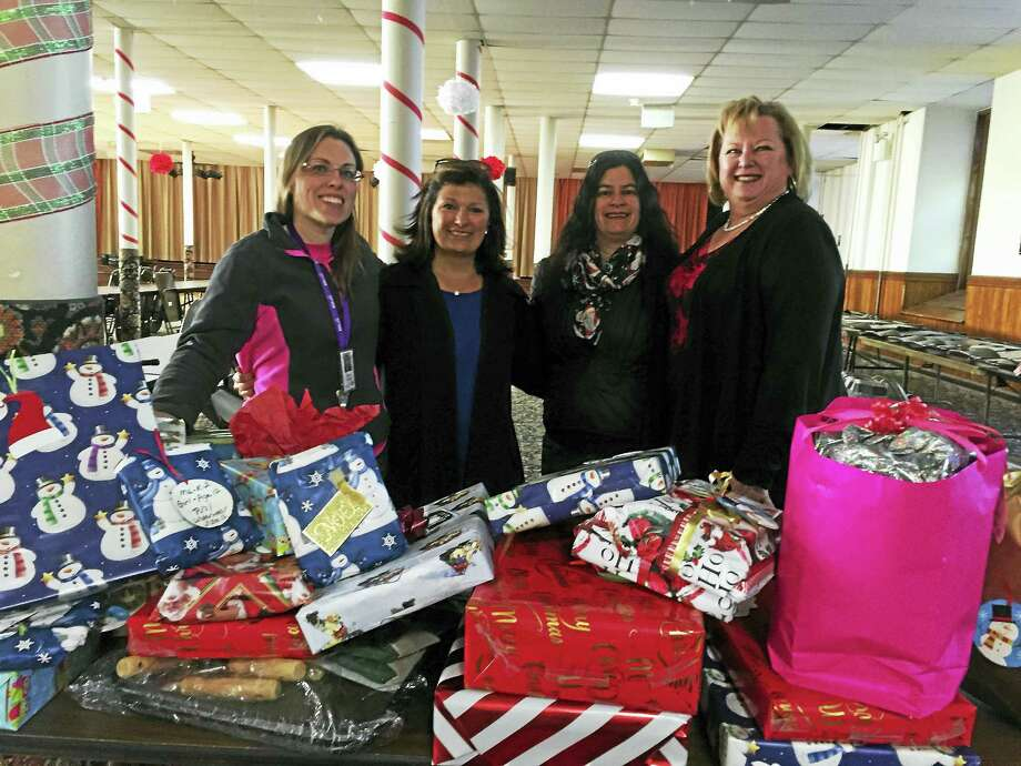 DiMatteo Group employees Rosemarie Esposito, second from left, and Barbara Gelozin, second from right, are photographed with Debra Soulsby, left, development coordinator at BHcare, and Tammy Burrell, right, chairwoman of the Holiday Drive and secretary of the BHcare board of directors, at Assumption Church in Ansonia. Photo: CONTRIBUTED PHOTO