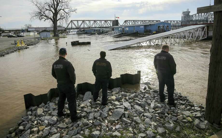 North Little Rock Firefighters look over the Arkansas River nearly flooding into the parking lot as they look to the east towards the Arkansas Inland Maritime Museum Friday morning, Jan. 1, 2016, in North Little Rock, Ark. Photo: Stephen B. Thornton/The Arkansas Democrat-Gazette Via AP / The Arkansas Democrat-Gazette
