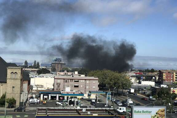 Smoke rose from a fire at a homeless encampment in Oakland Monday.