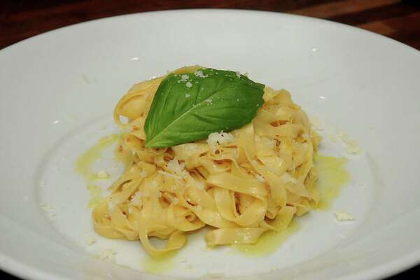 Fresh pasta dough is cut into fettuccine width at Weights & Measures.
