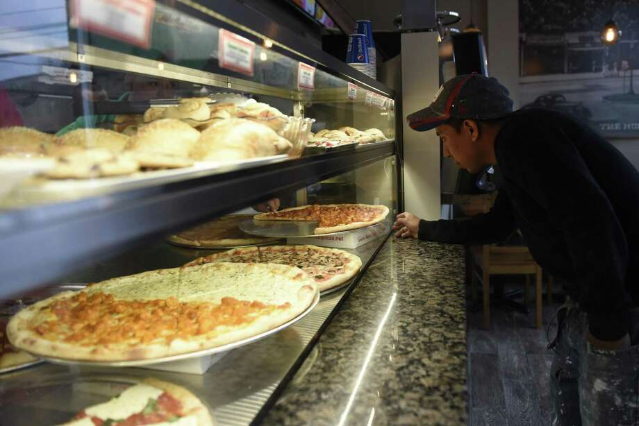 Port Chester, N.Y. resident Anderson Lopez takes a look at the by-the-slice pizza available at Fairfield Pizza in the Cos Cob section of Greenwich, Conn. Tuesday, Nov. 15, 2016. The new Greenwich location, which opened three weeks ago, joins the exisiting Fairfield, Stratford and Stamford locations of the by-the-slice pizza joint that also serves pasta, salads and sandwiches. Photo: Tyler Sizemore / Hearst Connecticut Media / Greenwich Time