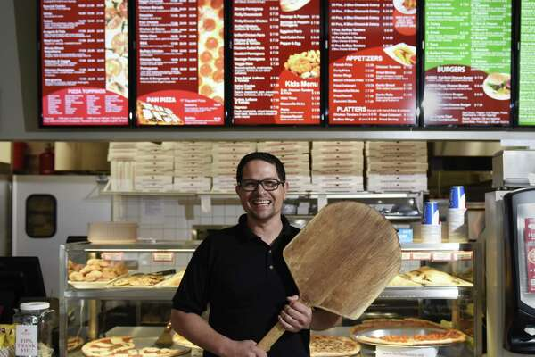Fairfield Pizza owner Luciano Zapf poses in front of the counter at Fairfield Pizza in the Cos Cob section of Greenwich, Conn. Tuesday, Nov. 15, 2016. The new Greenwich location, which opened three weeks ago, joins the exisiting Fairfield, Stratford and Stamford locations of the by-the-slice pizza joint that also serves pasta, salads and sandwiches.