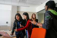 Mentor Ricky Trigalo, middle, directs Akanksha Bindal, right, and her team on how they could improve their presentation on the last day of the CodeHouse event, a three-day workshop teaching college women to engineer solutions for techs diversity chasm, on the VMware campus in Palo Alto on Friday, July 21, 2017.
