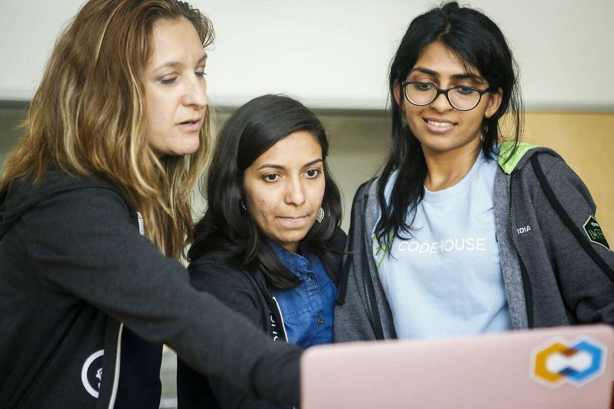 Mentor Ricky Trigalo, left, shows Rakshitha Bhat, middle, and Akanksha Bindal, right, where they could improve their presentation on the last day of the CodeHouse event, a three-day workshop teaching college women to engineer solutions for techs diversity chasm, on the VMware campus in Palo Alto on Friday, July 21, 2017.