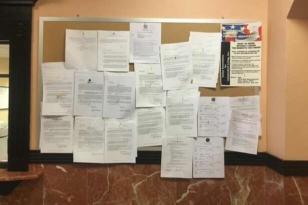 Various committee meeting agendas and public notices are posted outside the Webb County Clerk's office.