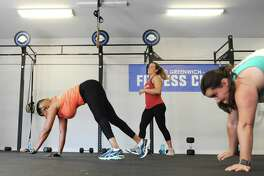 Group fitness instructor Chrissy Linegar, center, observes as class participants Sue Aarons, left, and Paige Elgarten do a bearcrawl during a group circuit workout at Old Greenwich Fitness Club in Old Greenwich, Conn. Thursday, July 20, 2017. Several former members of the Crossfit gym formerly at the location rebranded and renovated the facility to make it more family friendly.