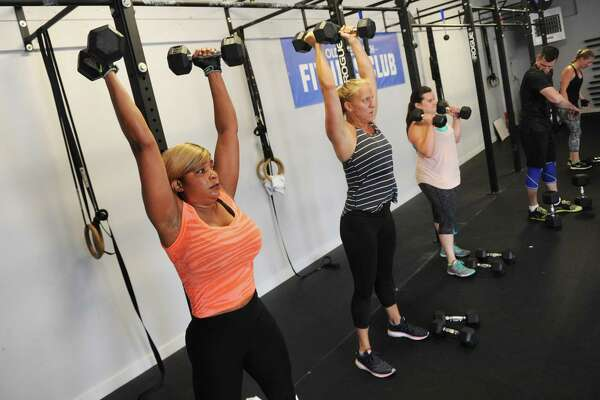 Sue Aarons, left, and others perform an overhead dumbbell lift during a group circuit workout at Old Greenwich Fitness Club in Old Greenwich, Conn. Thursday, July 20, 2017. Several former members of the Crossfit gym formerly at the location rebranded and renovated the facility to make it more family friendly.
