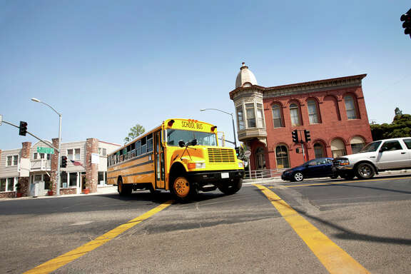 Yellow school bus turning corner at intersection traffic lights in California United States.