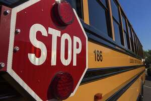 Traffic heading in both directions must stop for a school bus with flashing lights.