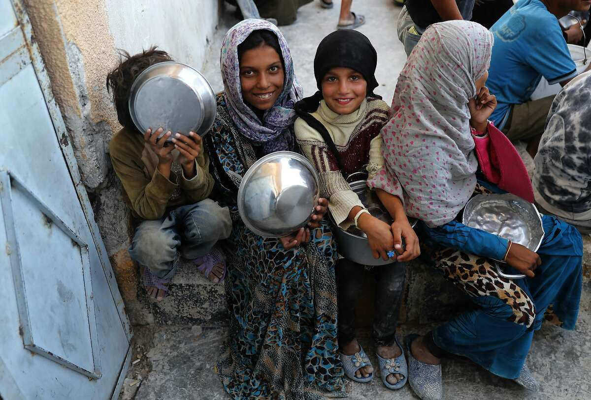 Syrian displaced girls who fled with their families the battle between U.S.-backed Syrian Democratic Forces and the Islamic State militants from Raqqa city, hold their pots as they wait to receive foods at the entrance of the main kitchen of a refugee camp, in Ain Issa town, northeast Syria, Wednesday, July 19, 2017. The U.S. military is supporting local Syrian forces in a campaign to drive IS from Raqqa. (AP Photo/Hussein Malla)