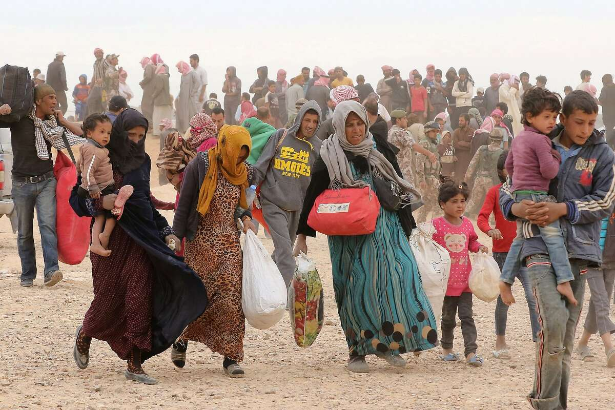 (FILES) This file photo taken on May 4, 2016 shows Syrian refugees carrying their belongings as they wait to enter Jordanian side of the Hadalat border crossing, a military zone east of the capital Amman, after arriving from Syria. Jordan's King Abdullah II has rejected calls to restore access to a border area where tens of thousands of Syrians are stranded, local media reported on August 15. Jordan declared the area around the Rukban border crossing a
