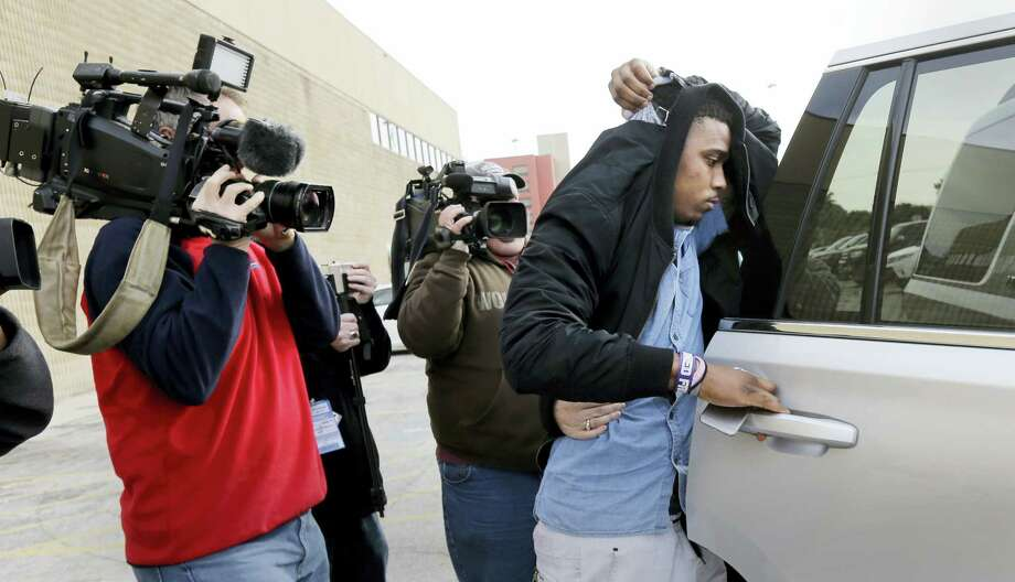 TCU quarterback Trevone Boykin, right, holds a jacket over his head as he is escorted from a detention center after he was released on bail Thursday in San Antonio. Photo: Eric Gay — The Associated Press   / AP