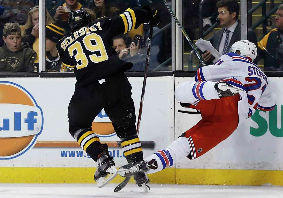The Bruins' Matt Beleskey checks the Rangers' Derek Stepan during Friday's game in Boston. Stepan suffered broken ribs on the play and will be out 4-6 weeks. Photo: Michael Dwyer — The Associated Press   / AP