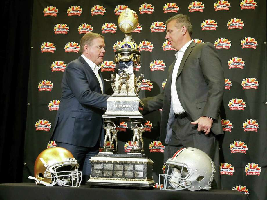 Notre Dame head coach Brian Kelly, left, and Ohio State head coach Urban Meyer shake hands during a news conference for the Fiesta Bowl Thursday in Scottsdale, Ariz. Photo: Rick Scuteri — The Associated Press   / FR157181 AP
