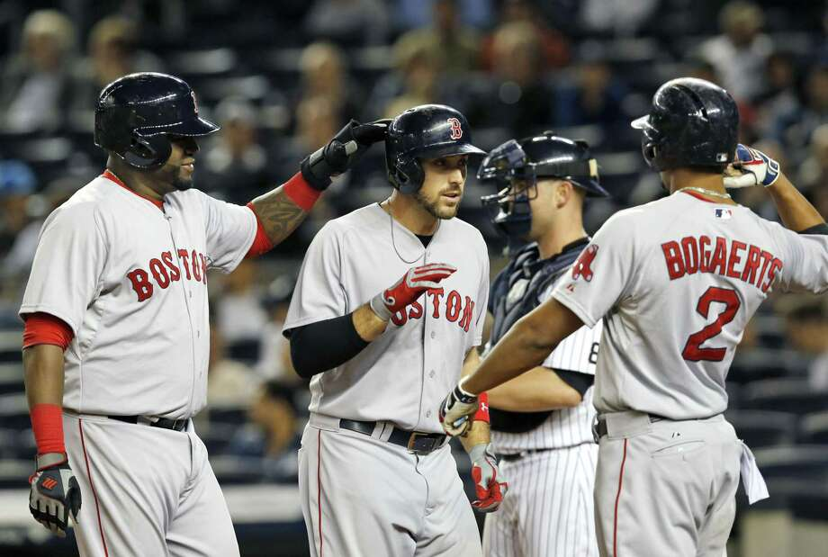 Red Sox designated hitter David Ortiz, left, congratulates Travis Shaw after he and Xander Bogaerts (2) scored on Shaw's first-inning three-run home run off New York Yankees starting pitcher Masahiro Tanaka. Photo: Kathy Willens  — The Associated Press   / AP