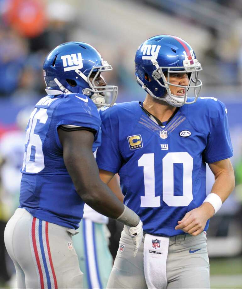 New York Giants running back Orleans Darkwa (26) celebrates with quarterback Eli Manning after rushing for a touchdown against the Dallas Cowboys last Sunday in East Rutherford, N.J. Photo: Bill Kostroun — The Associated Press   / FR51951 AP