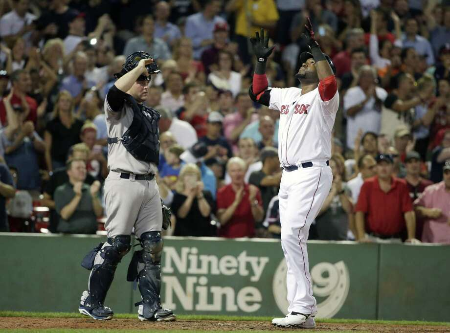 Red Sox designated hitter David Ortiz, right, celebrates his home run as Yankees catcher Brian McCann looks on in the fourth inning Monday. Photo: Steven Senne — The Associated Press   / AP