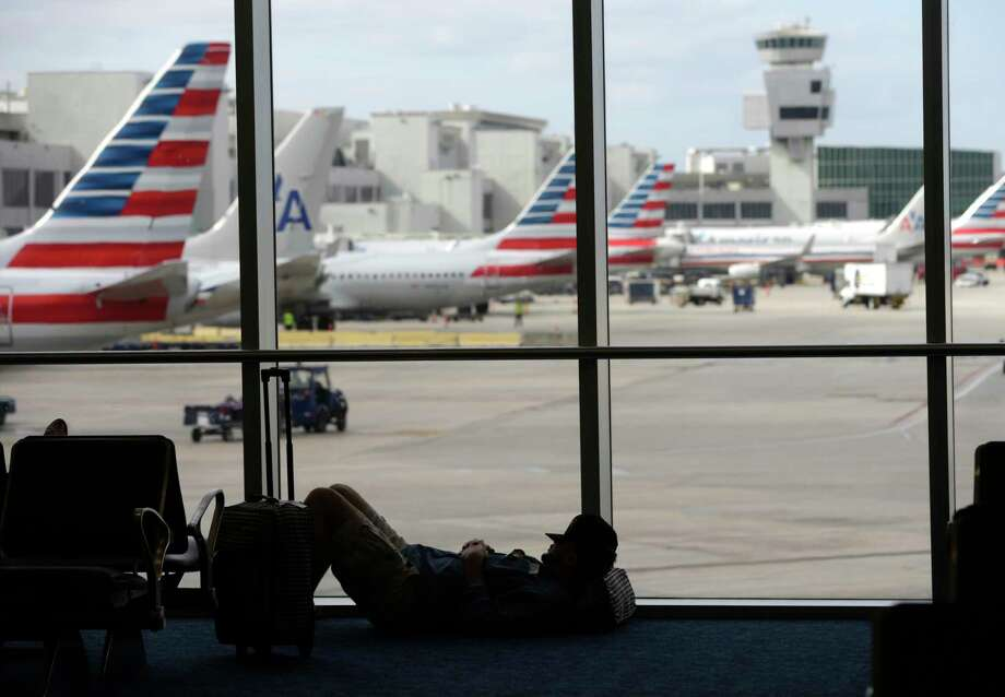 A traveler rests Nov. 24 on the floor as American Airlines aircraft are lined up the gates at Miami International Airport. On Cyber Monday, airlines are expected to launch flash sales on airfare. Photo: Associated Press File Photo   / AP