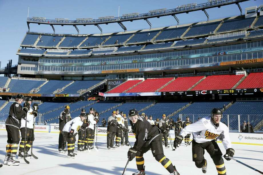 The Boston Bruins' Frank Vatrano, second from right, and Brett Connolly, right, skate Thursday during practice on the outdoor rink at Gillette Stadium in Foxborough, Mass. Photo: Michael Dwyer — The Associated Press   / AP