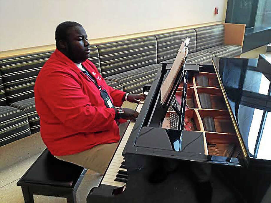 """Jeremiah Brown, 16, plays """"He is Love"""" on a piano at the Smilow Cancer Hospital, where he volunteers. Photo: (Brian Zahn -- New Haven Register)"""