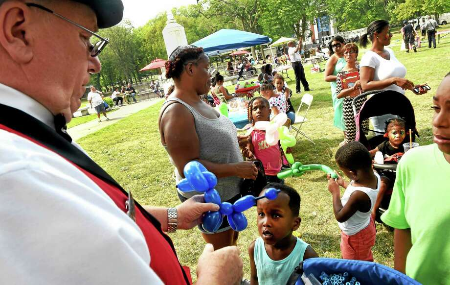 Ballon artist Leo Desilets of Orange, representing Friz Frizzles the Clown, left, creates a balloon dog for Kamil Mims, 5, of West Haven, lower left, during Jayden House Foundations free Care For Kids Youth Day Carnival 2015 on the New Haven Green Sunday, Aug. 30, 2015. Photo: Peter Hvizdak -- New Haven Register   / ©2015 Peter Hvizdak