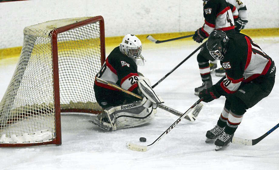 Branford's Zach Withington (10) clears the puck away from goalie Justin Edwards during a 2-2 tie with Hand. Photo: Dave Phillips — GameTime CT