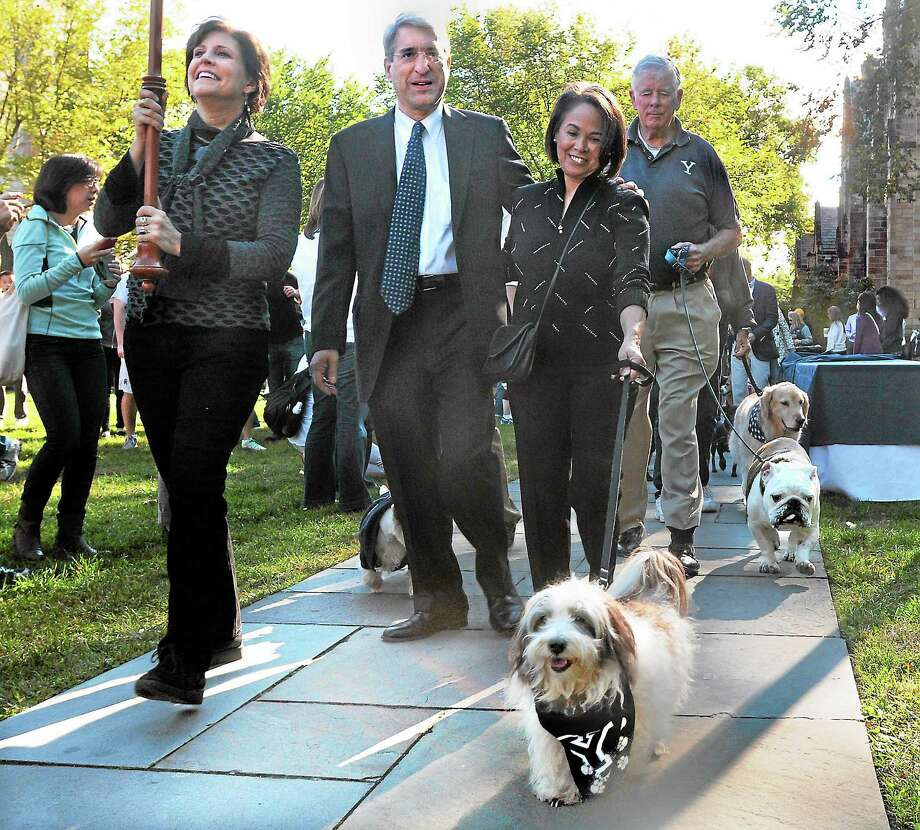 """Portia leads Yale President Peter Salovey and his wife, Marta Moret, during a """"Canine Kickoff"""" celebration of Salovey's inauguration as Yale president on Oct. 12, 2013. Associate Dean for the Arts Susan Cahan, left, leads the procession, while Handsome Dan XVII strides just behind with Chris Getman. Photo: (File Photo — New Haven Register)    / Mara Lavitt"""