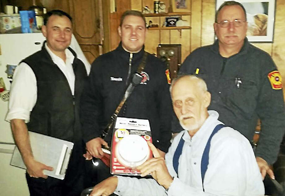 Senior Fire Inspector Anthony Fino, and Firefighters Jeff Maurutis and Mike Dunn went door to door in a mobile home community at 321 Bridgeport Ave., Milford, giving away free smoke detectors. William Lowell is seated. The effort comes after a man was found dead after a fire there about two weeks ago. Photo: Milford Fire Department