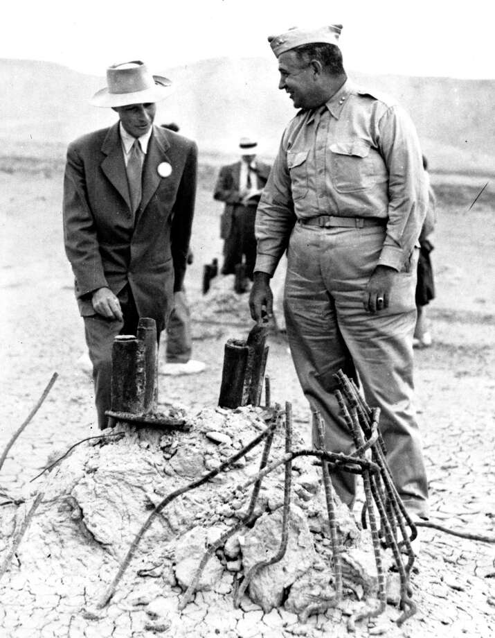 This Sept. 9, 1945, file photo Gen. Leslie R. Groves, right, and Dr. J. Robert Oppenheimer, who cooperated on the development of the atomic bomb, survey the area in Alamogordo, N.M., where a tower once stood before the test bomb exploded. A new PBS special looks into the creation of the atomic bomb in the city of Los Alamos and will feature newly-restored footage of nuclear weaponry. Photo: AP File Photo   / AP