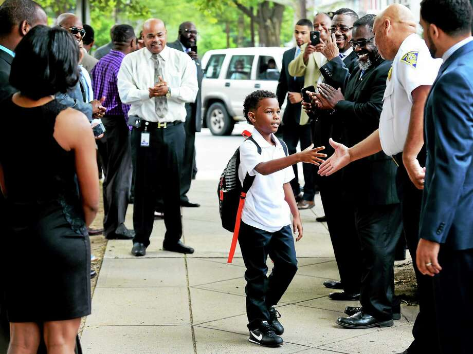Back to school on his birthday, Xavier Rivera, 8, of New Haven, a third-grader, walks through a receiving line and shakes hands with New Haven Police Lt. Herbert L. Sharp as Lincoln-Bassett School students, staff and parents are welcomed back on the first day of the new school year Monday morning. They were met  with applause, handshakes, cheering and encouraging words by New Haven Public Schools staff, local politicians, community leaders, New Haven police and fire officers, and residents. Photo: Peter Hvizdak — New Haven Register    / ©2015 Peter Hvizdak