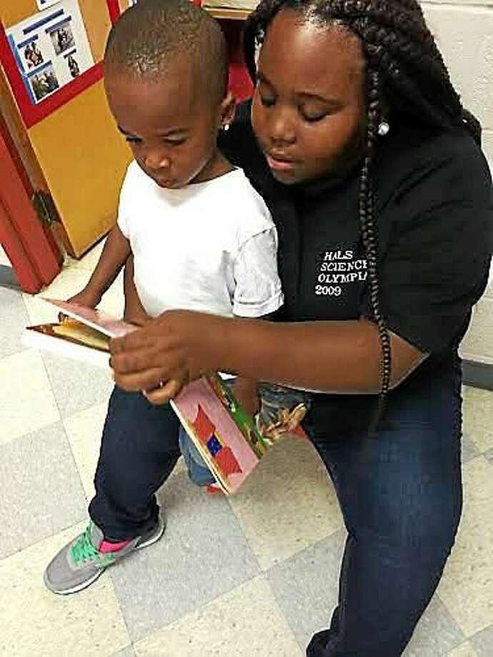 Fantasia reads to her son, Tijun, 2, at the Elizabeth Celotto Child Care Center in the basement of Wilbur Cross High School. Photo: CONTRIBUTED PHOTO — Rosa Ortiz