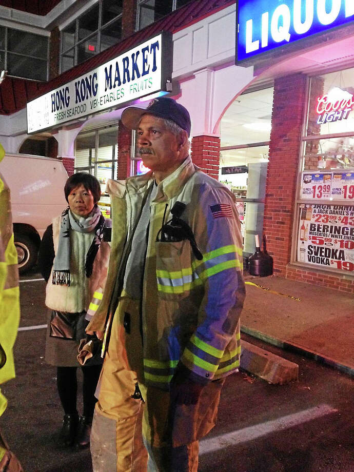 Michelle Guo, who helped with translating for the workers at Hao Sichuan, and Allingtown Deputy Fire  Chief Michael Esposito at the scene. Photo: Mary O'Leary — New Haven Register