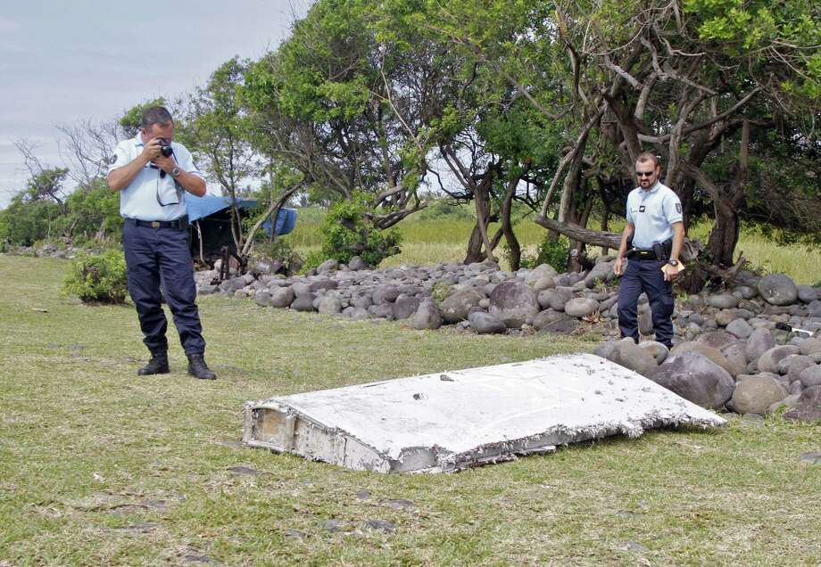 """In this photo dated July 29, 2015, French police officers look over a piece of debris from a plane in Saint-Andre, Reunion Island. Air safety investigators, one of them a Boeing investigator, have identified the component as a """"flaperon"""" from the trailing edge of a Boeing 777 wing, a U.S. official said. Flight 370, which disappeared March 8, 2014, with 239 people on board, is the only 777 known to be missing. Photo: AP Photo/Lucas Marie   / AP"""