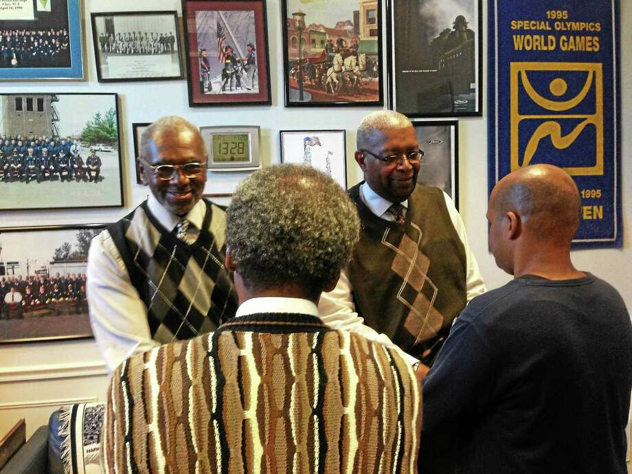 Project MORE's Dennis Daniels, left, and Morris Moreland greet two clients of the agency, which serves ex-offenders. Photo: Journal Register Co.
