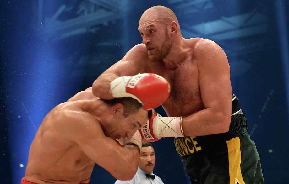 Ukraine's Wladimir Klitschko, left, and Britain's Tyson Fury exchange blows in a world heavyweight title fight Saturday in Duesseldorf, Germany. Photo: Martin Meissner — The Associated Press   / AP