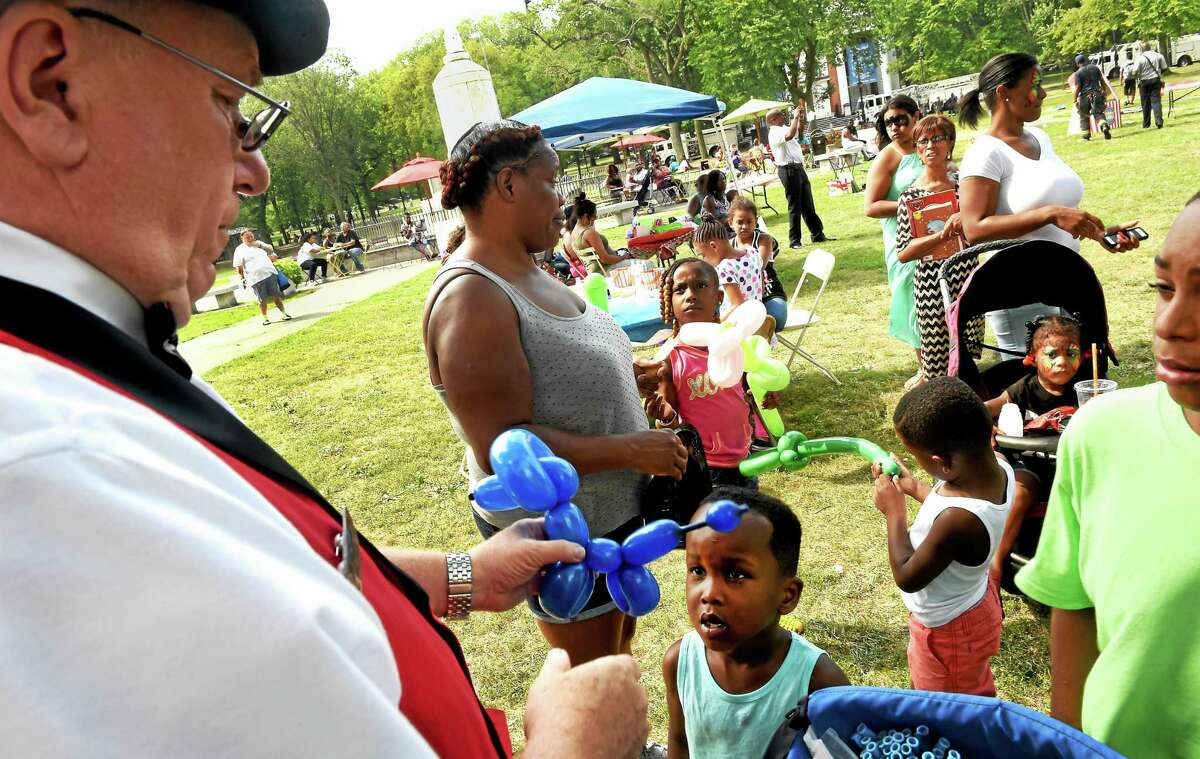 (Peter Hvizdak - New Haven Register) Ballon artist Leo Desilets of Orange, representing Friz Frizzles the Clown, left, creates a ballon dog for Kamil Mims, 5, of West Haven, lower left, during Jayden House Foundations free Care For Kids Youth Day Carnival 2015 on the New Haven Green Sunday.