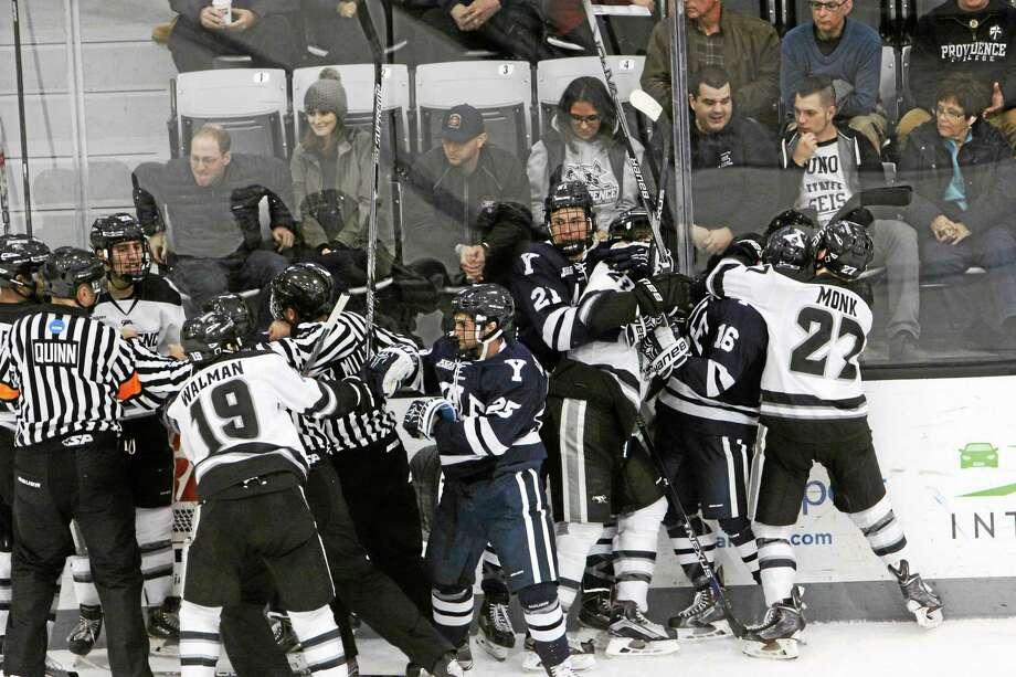 Members of the Yale and Providence hockey teams scuffle after the end of the second period on Saturday. Photo: Photo Courtesy Of Yale Athletics