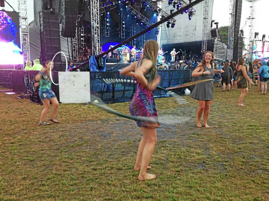Four young women from Marshfield, Massachusetts, hula-hoop in the rain as Strangefolk plays Thursday at the opening day of the Gathering of the Vibes Festival at Seaside Park in Bridgeport. Photo: Mark Zaretsky — New Haven Register