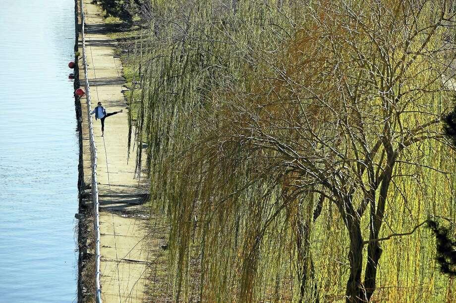 A woman works out on a walkway near an artificial shore wall. Photo: Washington Post Photo By Matt McClain  / The Washington Post