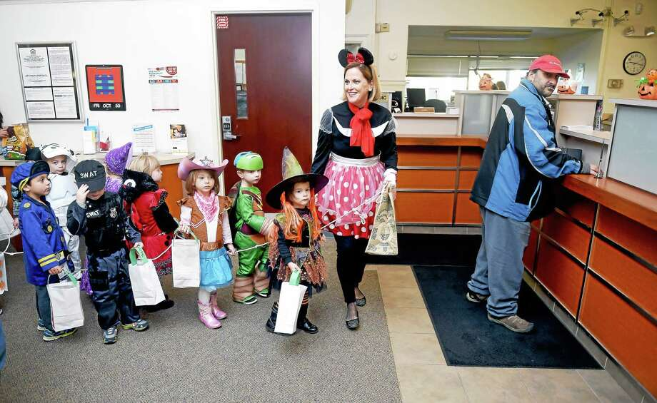 Preschool teacher Joan Dougherty, center, dressed as Minnie Mouse, leads her class from the Old Stone Church Playschool through First Niagara Bank on Main Street in East Haven Friday. At right is Robert Mandato of New Haven. Photo: Arnold Gold — New Haven Register