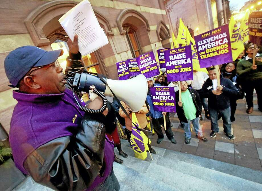 Alberto Bernardez, assistant supervisor of SEIU Local 32BJ of commercial building janitors union leads a rally Dec. 21 in front of New Haven City Hall. Photo: Peter Hvizdak — New Haven Register   / ©2015 Peter Hvizdak