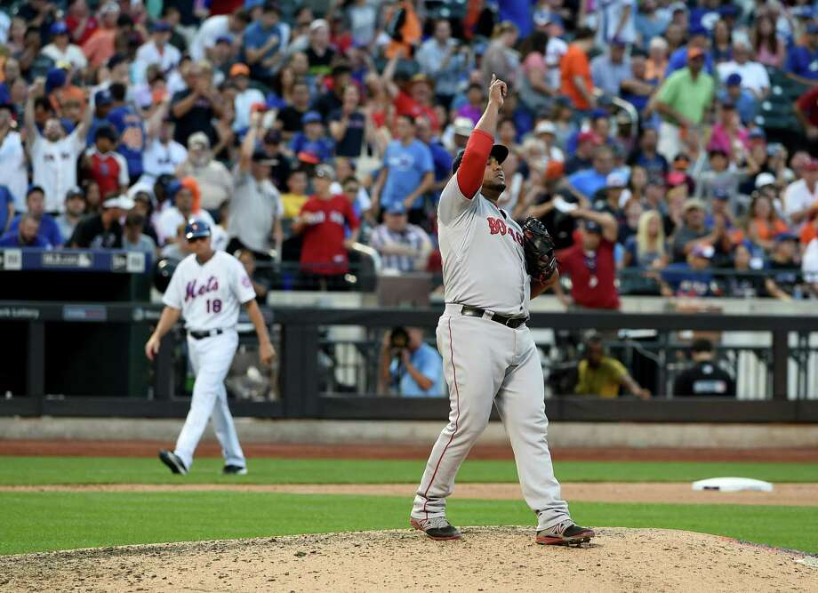 Third base coach Tim Teufel, rear, walks off the field as Boston reliever Jean Machi celebrates the Red Sox's 3-1 win over the Mets on Saturday in New York. Photo: Kathy Kmonicek — The Associated Press   / FR170189 AP